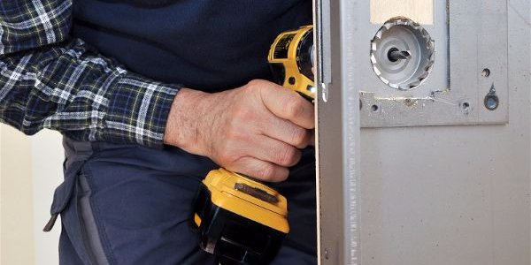 Locksmith drilling into door to install lock